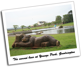 View of a carved wooden bear, boating lake, duck pond and green at Youngs Park, Goodrington